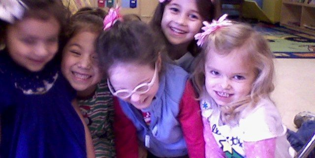 Five laughing young girls, together in a group, lie propped up on their hands while on the floor in a pre-school classroom.