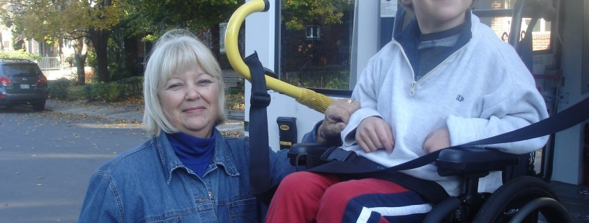 A smiling woman stands next to a smiling young boy, who is seated in a wheelchair that is being loaded onto a white bus.