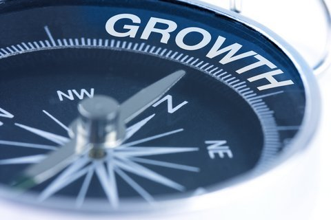 """A black compass face with the silver needle pointing towards the word """"Growth""""."""