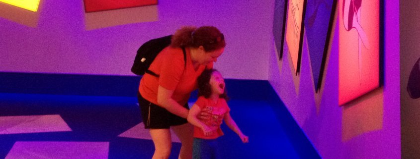 A smiling mother supporting her laughing daughter from behind as they stand in a room with colorful glowing shapes and pictures