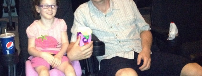 A smiling young girl in a pink adaptive seat and her father, with popcorn and drinks, in seats at a movie theater.