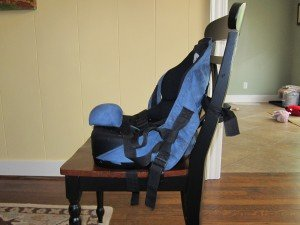A powder blue and black adaptive seat is pictured from the side strapped onto a black and brown dining chair.