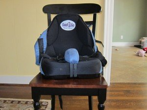 A powder blue and black adaptive booster seat is pictured from the front strapped onto a black and brown dining chair.