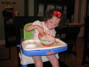 A young girl with brown hair, pink bow, and round pink glasses eats from a bowl sitting at a Fisher Price high chair.