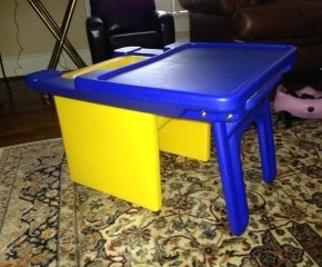 A short, yellow plastic cube shaped chair is pictured with an attachable blue desk for flexible adaptive seating