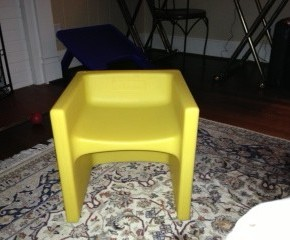A short, yellow plastic cube shaped chair is pictured straight on showing two heights for flexible adaptive seating