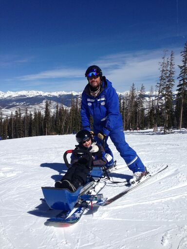 A young boy is skiing in an adaptive skiing sled with an adult behind him holding the push bar.