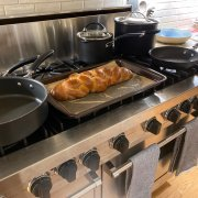 A golden-brown loaf of braided challah on a parchment paper covered tray resting atop the stovetop burners.