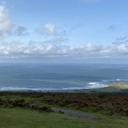 A view over the vast dark blue Atlantic Ocean from high on the coast of Ireland with a blanket of grey clouds drifting above.