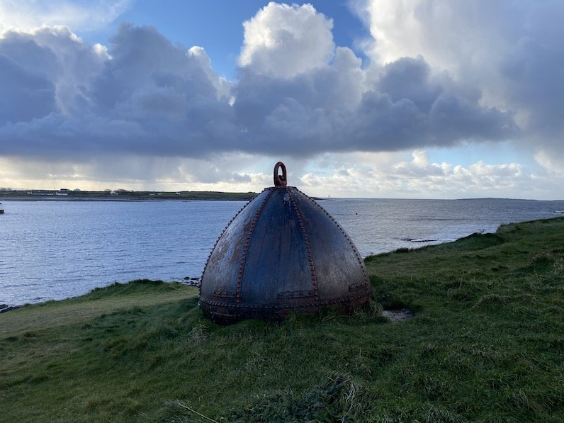 An old conical metal buoy standing on a windswept headland overlooking the ocean under a cloudy blue sky in the fading daylight