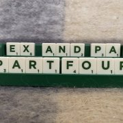 White Scrabble game tiles in a dark green rack spelling the words: 'EX AND PA PART FOUR'.