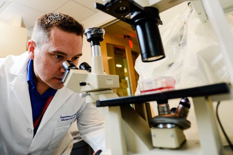 Dr. Michael Kruer, at the microscope in his lab, studies the genetic causes of CP.
