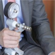The hand of a man, wearing a grey suit, grasping a grip strength measurement device.