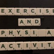 White Scrabble game tiles on a table spelling the words: 'EXERCISE AND PHYSICAL ACTIVITY'.