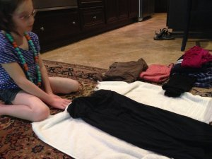 Cerebral palsy employment preparation starts early -- young Lilly w sits on the floor while learning to fold laundry