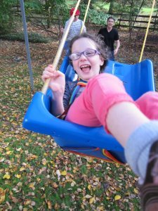 Cerebral palsy causes are not always known. Lily is pictured with a big smile in a blue swing at the end of its pendulum motion