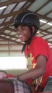 An African American boy with a helmet is grinning as he rides a horse in an adaptive program providing people with cerebral palsy recreation opportunities that are also therapeutic.