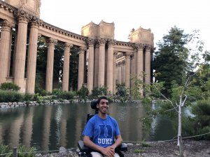 Cerebral Palsy and Traveling -- A young Indian man, smiling in a blue t-shirt that says 'Duke' sits in his wheelchair in front of a reflecting pool while visiting the Palace of Fine Arts in San Francisco