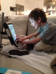 Cerebral palsy communication devices can be very helpful -- A young boy sits crossed-legged on his bed while using his communication device