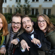 Four laughing young adults in a line; two young men in the middle with two young women on either side of them pose for a photo.