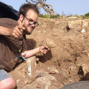 A smiling young man with glasses, short hair and a beard lies on his side at an archaeological site giving the thumbs up sign.