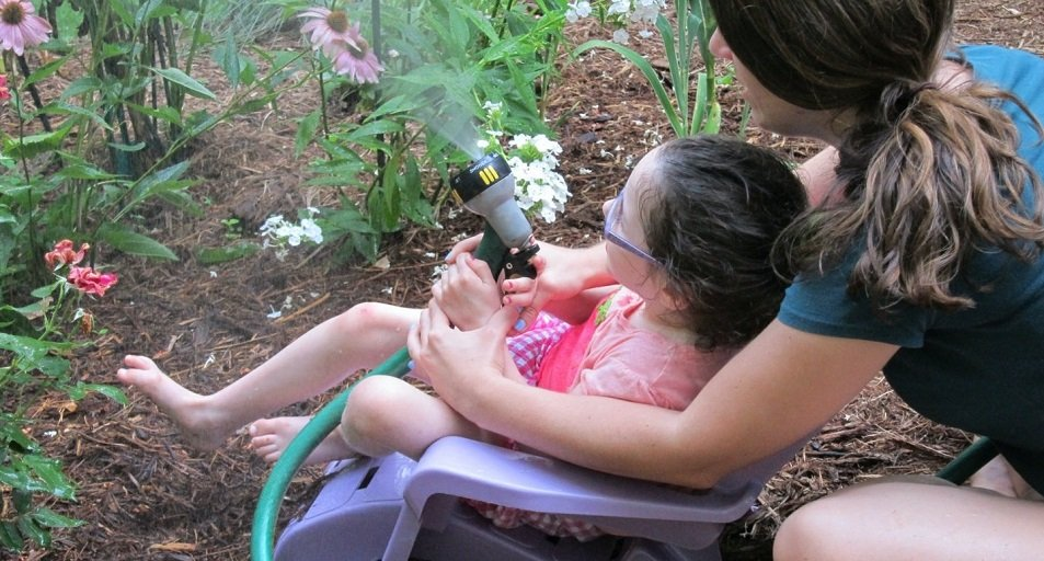 Image of Lillian with a water sprayer in the garden