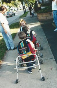 The Shrader Triplets head off to pre-school two with their walkers but all three with matching backpacks.