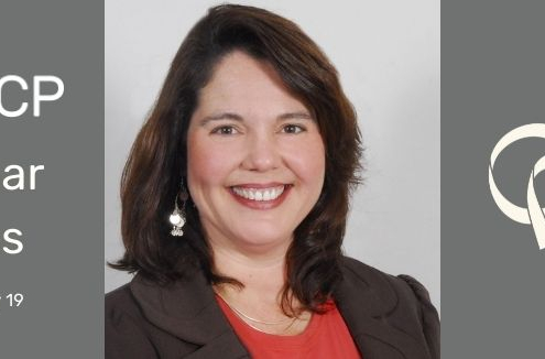 Dr. Mary Gannotti with shoulder length brown hair smiles broadly in red blouse and brown blazer
