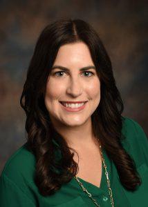 Laura Gilbert, DO, a pediatric neurologist, with shoulder length brown hair and a dark green shirt, smiles broadly.