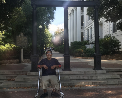 Marquise Lane sits down on his aluminum walker smiling with a wrought iron arch and a building with white pillars behind him