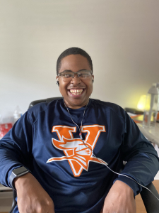 Marquise Lane, with a beaming smile and glasses sits listening to music in his college dorm with a navy football sweatshirt