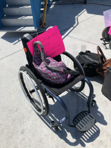 Traveling with a wheelchair tips: A spare manual wheelchair is pictured on the tarmac with a bright pink instructional sign