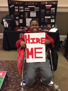 """Marquise Lane, in a red sweatshirt at a job fair, sits holding a large white sign with the words """"Hire Me"""" in red"""