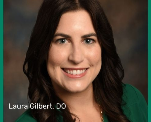 Dr. Laura Gilbert, with shoulder length brown hair and a green shirt, smiles broadly. Her dystonia abstract won her an award