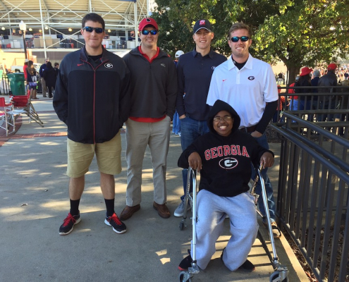 Marquis Lane, a young African American man, seated wearing a navy Georgia sweatshirt with four friends behind him at a stadium