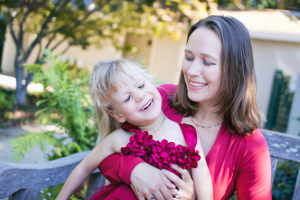 Tanya Sheckley in a red blouse smiles at her daughter Eliza who is wearing a magenta taffeta party dress with red flowers in the neckline.