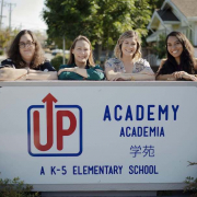Four smiling women stand outdoors on a sunny day behind the UP Academy sign with their arms folded and resting on top.