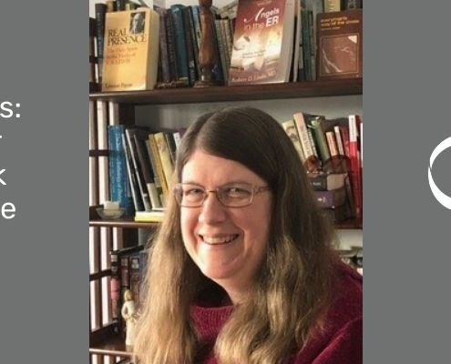 Heather Hancock, pictured with long brown hair and red shirt, wire rimmed glasses with a book case behind her is an editor