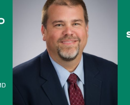 A green page banner with a headshot of Dr. Wade Shrader. A smiling man with short brown hair and beard wearing a dark suit.